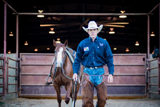 Hunter Meinzer stands outside his training barn with his horse